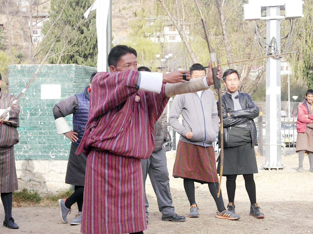 Typical Sunday activities to Bhutanese men gathering in their stadium to play archery